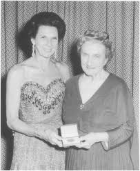 Belinda Quirey receiving her MBE, with Dame Beryl Gray